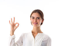 Woman showing okay. Young pretty woman in white blouse showing okay on white background in studio Royalty Free Stock Photography