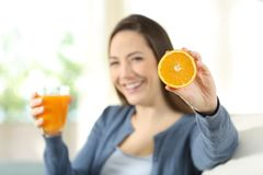 Woman showing a orenge and a juice. Happy woman showing a orenge and a juice sitting on a couch in the living room at home Royalty Free Stock Image
