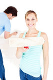 Woman showing paint brush while boyfriend painting. In the background Royalty Free Stock Photography