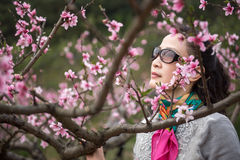 Woman showing in peach orchard Royalty Free Stock Image