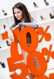 Woman showing the percentage of sales on stylish shoes Royalty Free Stock Image