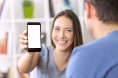 Woman showing phone screen to a friend. Woman showing a smart phone screen to a friend at home Stock Photo