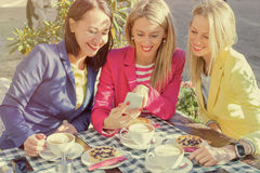 Woman showing pictures to her friends on mobile phone royalty free stock image