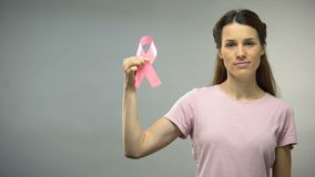 Woman showing pink ribbon into camera, international breast cancer awareness. Stock footage stock video