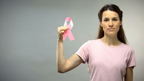 Woman showing pink ribbon into camera, international breast cancer awareness stock photography