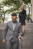 Woman showing power over man in business setting Stock Photo