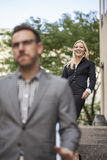 Woman showing power over man in business setting Stock Photos