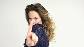 Woman showing prohibition gesture. Pretty woman in dark blue dress showing prohibition gesture with finger and looking at camera with condemnation stock footage