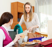 Woman showing purchases  to girlfriend at  home Stock Photography