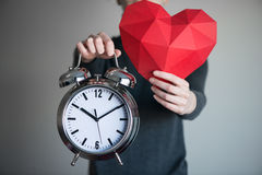 Woman showing red polygonal heart shape and alarm clock Stock Photo
