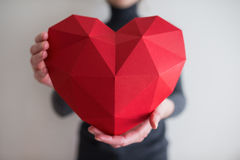 Woman showing red polygonal paper heart shape Royalty Free Stock Images