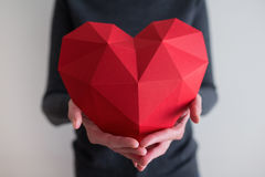 Woman showing red polygonal paper heart shape Stock Photos