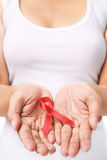 Woman showing red ribbon to support AIDS cause