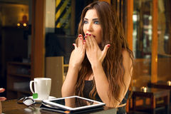 Woman showing a shocking reaction in a cafe Stock Photography