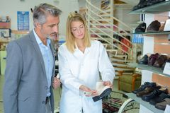 Woman showing shoes to customer. Customer stock image