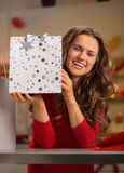 Woman showing shopping bag in decorated kitchen Royalty Free Stock Photo