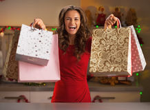 Woman showing shopping bags in christmas decorated kitchen Royalty Free Stock Images