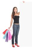 Woman showing shopping sign copy space. Woman shopping sign. Shopper showing blank billboard sign while standing with many shopping bags. Full length picture of Stock Image
