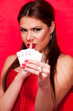 Woman showing shush and holding poker of aces Stock Images