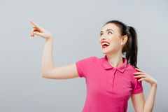 Woman showing sign looking happy excited. Advertisement.  Stock Photos