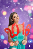 Woman showing sign of New Year 2016. Smiling young woman showing decorative sign of New Year 2016 Stock Images