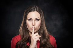 Woman showing silence sign the finger near lips. Stock Images