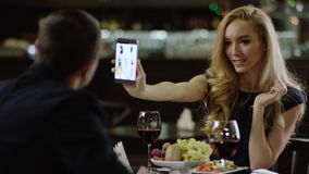 Woman showing a site on smartphone phone to a man in cafe stock footage