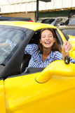 Woman showing sitting inside of her new sports car. Happy woman showing sitting inside of her new yellow sports car Stock Photos