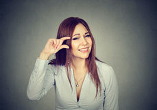 Woman showing small amount size gesture with fingers. Woman showing small amount size gesture with hand fingers on gray wall background. Human emotion facial royalty free stock images