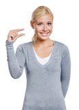 Woman showing small amount of something. With fingers, isolated on white stock photography