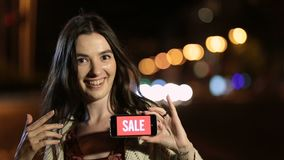 Woman showing smartphone with sale advertising stock video footage