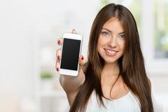 Woman showing smartphone screen. Smiling woman showing smartphone screen Royalty Free Stock Photography