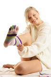 Woman showing sock. Laughing woman showing sock sitting on bed isolated on white background royalty free stock images