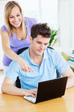 Woman showing something on the computer. To his boyfriend  standing in the living-room Royalty Free Stock Image