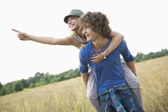 Woman showing something while enjoying piggyback ride on man in field Royalty Free Stock Photos