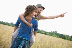 Woman showing something while enjoying piggyback ride on man in field. Woman showing something while enjoying piggyback ride on men in field Royalty Free Stock Photo