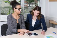 Woman is showing something at a tablet Stock Photography