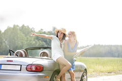 Woman showing something to female friend with map while leaning on convertible Royalty Free Stock Photo