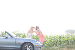 Woman showing something to female friend while reading map on convertible Royalty Free Stock Photography