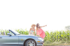 Woman showing something to female friend while standing by convertible Stock Photos