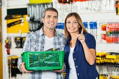 Woman Showing Something To Man In Hardware Store. Woman showing something to men holding basket of tools in hardware store Royalty Free Stock Images