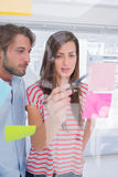 Woman showing sticky note to her colleague Stock Images