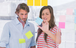 Woman showing the sticky note to her colleague Stock Photo