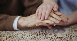 Woman touching elderly man hands and supporting Senior Man