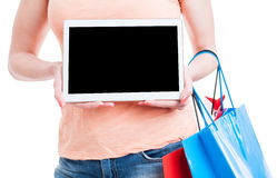 Woman showing tablet blank screen and holding shopping bags Royalty Free Stock Photography
