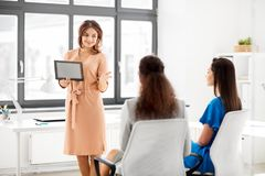 Woman showing tablet pc to business team at office Royalty Free Stock Photography
