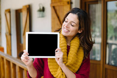 Woman showing tablet screen outside home on autumn Royalty Free Stock Images