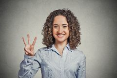 Woman showing three fingers sign gesture. Closeup portrait young curly hair woman giving three fingers sign gesture isolated grey wall background. Positive human Stock Images