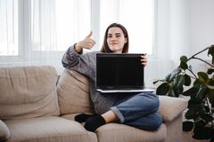 Woman showing thumb up gesture near empty screen stock photos