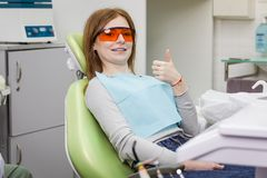 Woman showing thumb up sign at dentist`s office clinic. Woman showing thumb up sign at dentist`s office Royalty Free Stock Photo